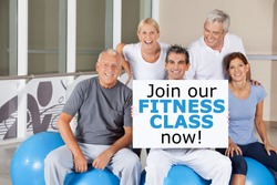 "Happy senior group holding a ""Join our fitness class now"" sign"