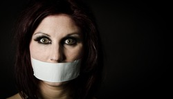Portrait of scared woman with tape over her mouth