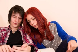 Student couple looking at something on a smarthphone