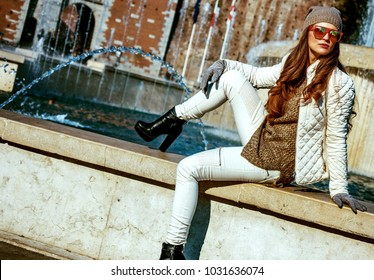 Rediscovering things everybody love in Milan. modern woman in Milan, Italy sitting near fountain