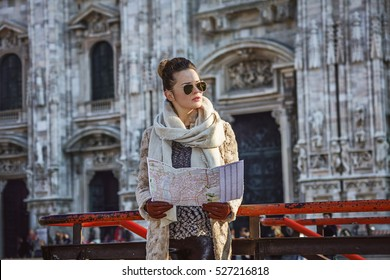 Rediscovering things everybody love in Milan. elegant woman in fur coat and sunglasses in the front of Duomo in Milan, Italy with map looking into the distance