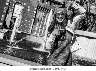 Rediscovering things everybody love in Milan. smiling young woman near Sforza Castle in Milan, Italy with hands framing