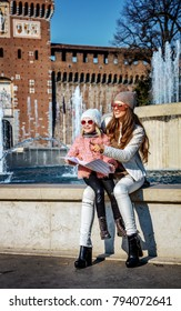 Rediscovering things everybody love in Milan. Full length portrait of smiling modern mother and daughter tourists in sunglasses in Milan, Italy holding map and pointing