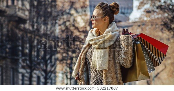 Rediscovering things everybody love in Milan. Full length portrait of elegant traveller woman with shopping bags near Sforza Castle in Milan, Italy looking into the distance