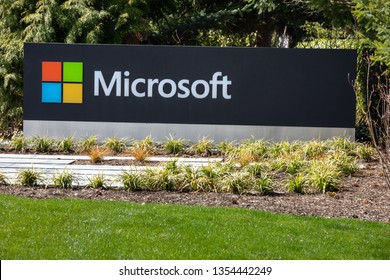 Redmond, Washington / USA - March 28 2019: Close up on a Microsoft sign at the headquarters for the cloud computing and software company, with green tree background and space for text on bottom