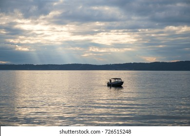 Redondo Beach, WA, USA Aug. 18, 2017: Lone fishing boat with a single person aboard on the reflective waters of Puget Sound, Washington at sunset