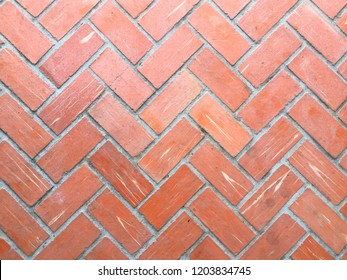 Red-orange Clay brick wall in 45 degree zig zag pattern. Vintage concept. Construction background.