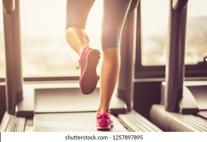 Reduce calories in your body. Female muscular feet in sneakers running on the treadmill. Close up.