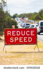 Reduce speed caution sign at roadside, with many cars in traffic congestion in blurred background.