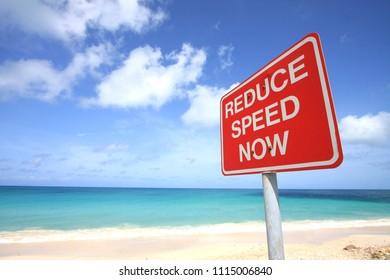 Reduce Speed Now road sign alongside Darkwood Beach, Antigua