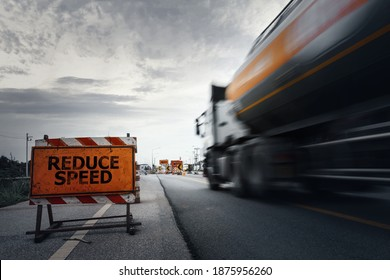 Reduce speed road sign on a countryside road with blurry speed truck,dark and dramatic scene with low-speed shutter.