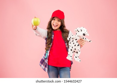Reduce stress. Girl little fashionable schoolgirl with backpack carry soft toy dog and hold apple. Healthy lifestyle. Mental and physical wellbeing. Schoolgirl daily life. Stylish schoolgirl.
