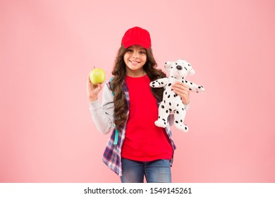 Reduce stress. Healthy lifestyle. Mental and physical wellbeing. Schoolgirl daily life. Stylish schoolgirl. Girl little fashionable schoolgirl with backpack carry soft toy dog and hold apple.