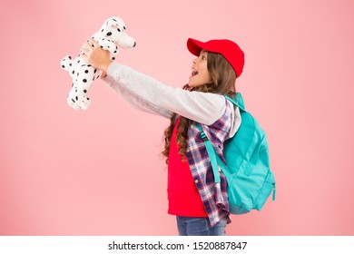 Reduce stress. Schoolgirl daily life. Schoolgirl street style clothes. School club. Stylish schoolgirl. Girl little fashionable cutie with backpack carry soft toy dog. Take favorite toy with you.