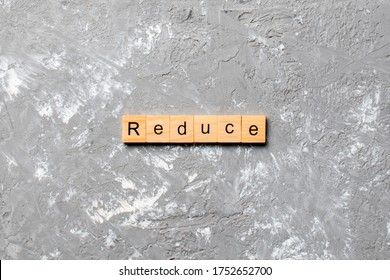 reduce word written on wood block. reduce text on cement table for your desing, concept.