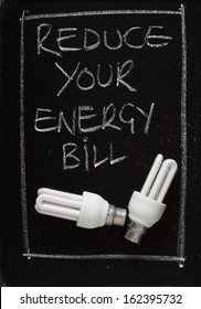 Reduce Your Energy Bill written on a blackboard with two energy efficient light bulbs. As utility companies increase the cost of electricity we look for ways to save money for the household budget