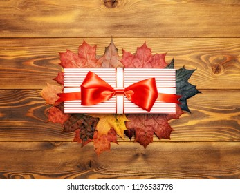 Red-white gift box on wooden board. Copy space. Holidays concept