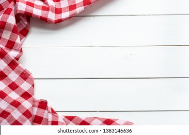 Red-white kitchen tablecloth on a white table. View from the top.