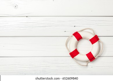 Red-white lifebuoy on white wooden board