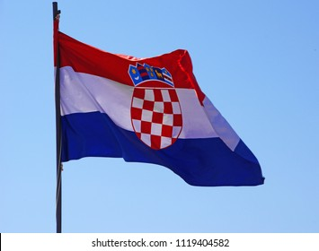 the red-white-blue with a checker in the middle and a crown, flag of croatia flutters on the mast