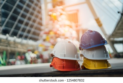 Red,white,yellow and blue hard safety helmet hat for safety project of workman as worker or engineer,on staircase and floor.Business Industrial Safety Health Employee Concept .