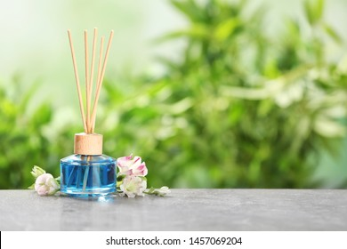 Reed air freshener and flowers on grey table against blurred green background. Space for text