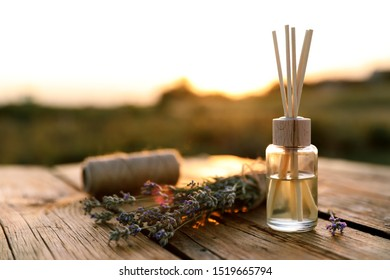 Reed air freshener and fresh lavender flowers on wooden table in field. Space for text