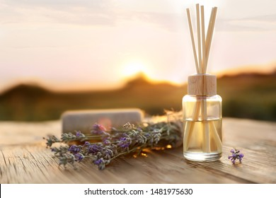 Reed air freshener with oil and fresh lavender flowers on wooden table outdoors. Space for text