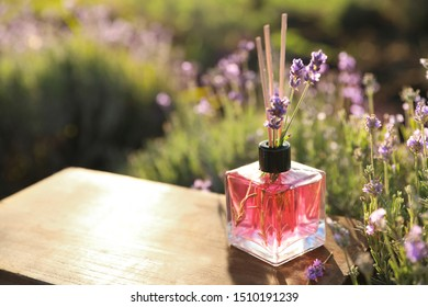 Reed air freshener with oil and fresh lavender flowers on wooden table in blooming field. Space for text