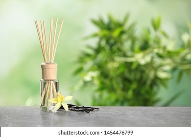 Reed air freshener with vanilla flower and sticks on grey table against blurred green background. Space for text