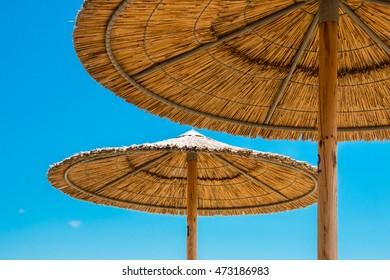 Reed Beach Umbrellas Against Blue Sky