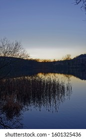 Reed beds and reflections in the calm waters of Clunie Loch at dusk on  a cold Christmas day.