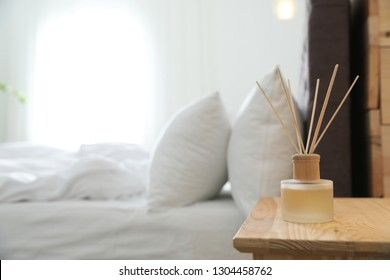 Reed diffuser on nightstand near bed in room. Modern interior