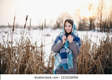 reed portrait of a girl with a scarf in a cage. winter portrait of a beautiful girl. the girl is cold she is heated with a scarf. happy girl in winter bounces. brunette by the reeds