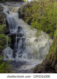 The Reekie Linn waterfall on the River Isla, Perthshire, Scotland, in full spate through the tree-lined precipitous gorge.