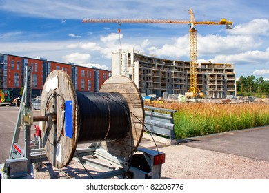 A reel of heavy coaxial cable used for cable-TV underground construction, and the construction site in the background
