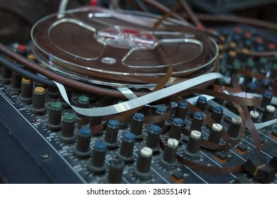 Reel to reel tape on an old mixing console, indoor shot with selective focus
