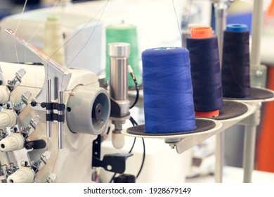 Reels of textile yarn blue thread at industrial weaving manufacturing machine