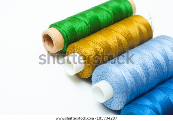 reels of thread on white table, not isolated