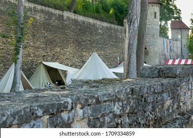 Reenactment of a medieval scene against the historical backdrop of an old city wall, village with tents of various designs with details of fabrics and pegs, ropes and bracing, view of tents