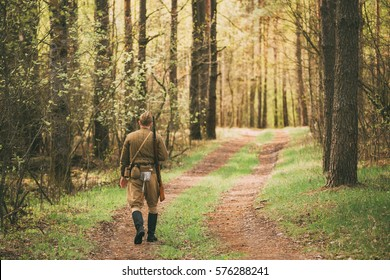 Re-enactor Dressed As Soviet Russian Red Army Infantry Soldier Of World War II Marching Along Forest Road At Spring Season.