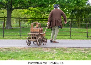 reenactor in medieval costume pulling medieval drinks cart