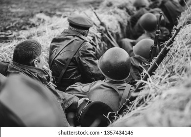 Re-enactors Dressed As World War II Russian Soviet Red Army Soldiers Hidden Sitting In Trench. Photo In Black And White Colors. WWII WW2.