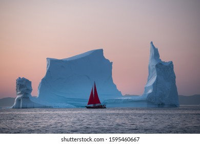 Ref sail in the beautiful landscape with large icebergs