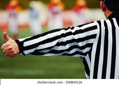 Referee of the american football on the field, american football referee gestures with big team in of focus on background