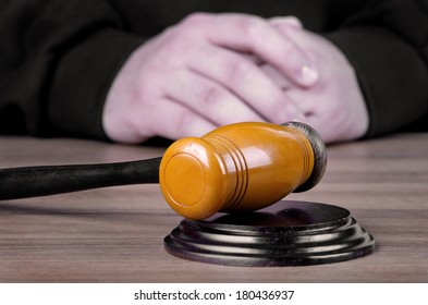 Referee hammer and a man in judicial robes in court