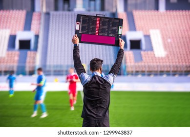 Referee holds the table for additional time. Football, soccer photo