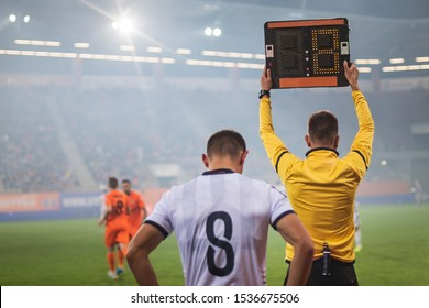 Referee shows players substitution during soccer match.