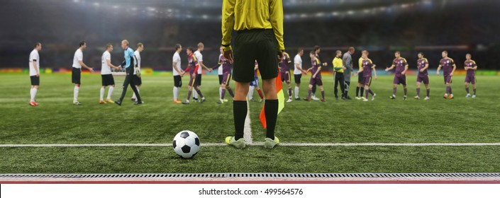 The referee soccer game stands on the field before the game, ready to blow the whistle. Soccer Team greet each other at the stadium before the match