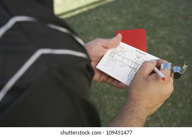 Referee writing in his report book while holding a red card